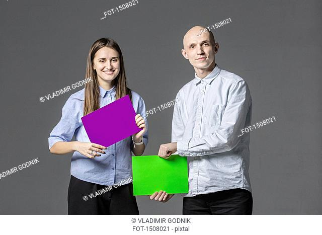 Portrait of business people holding placards against gray background