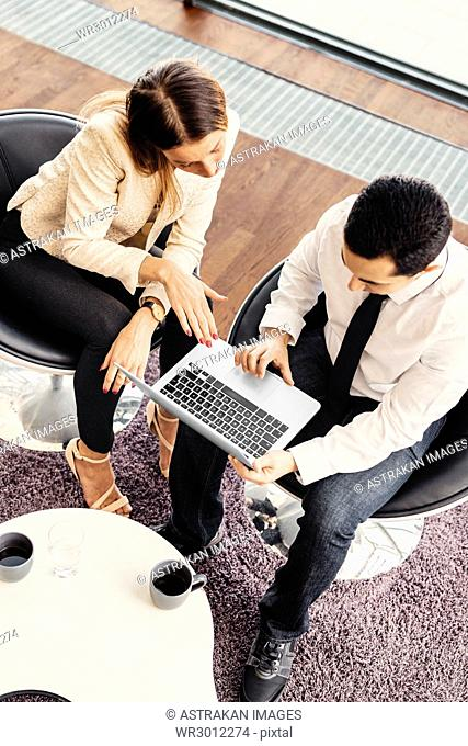 High angle view of two colleagues working on laptop