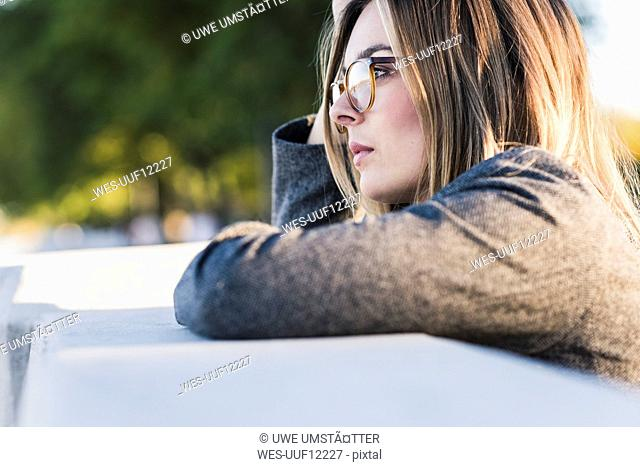 Thoughtful young woman leaning on a wall