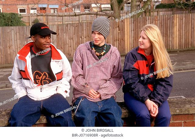 Multiracial group of youths sitting on brick wall smiling
