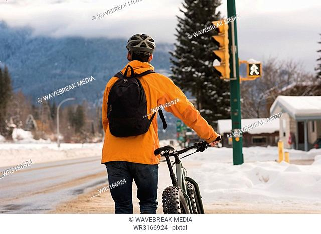 Man walking with his cycle on sidewalk during winter