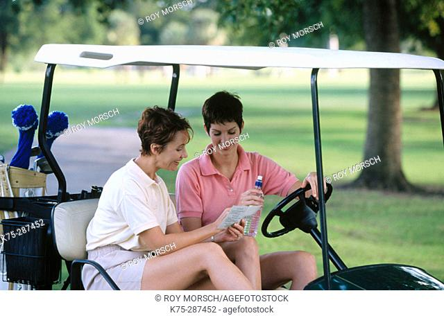 gwo women checking their scorecard on golf course