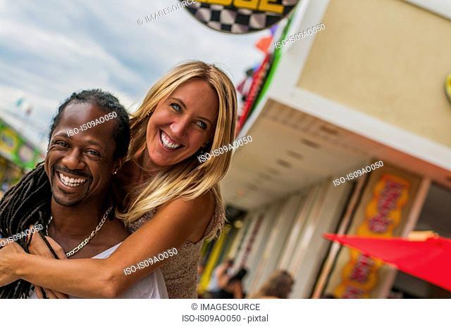 Multi ethnic mature couple sharing piggyback at amusement park