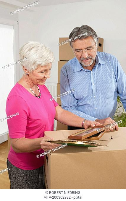 Senior couple looking at picture frames in new apartment, Bavaria, Germany
