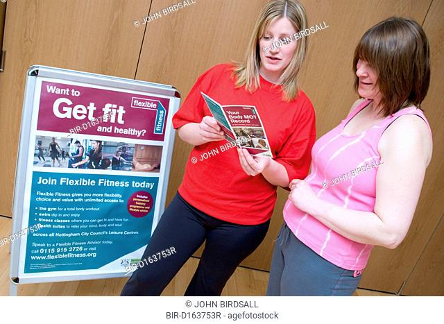 Fitness instructor going through a body MOT leaflet with a member at her sports leisure centre