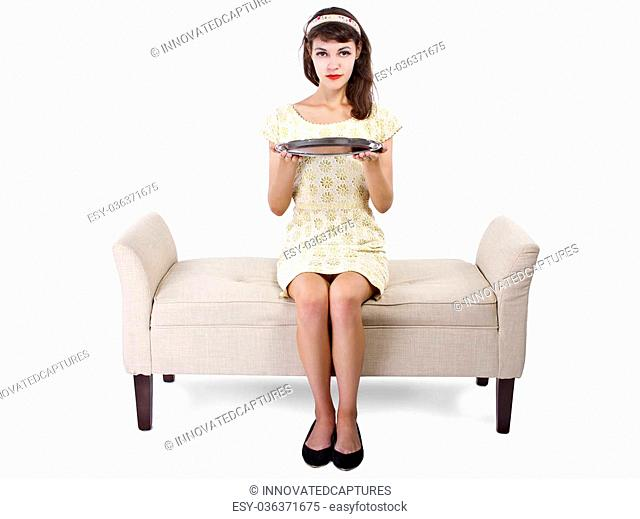 woman seated on a chaise holding a blank tray for composites
