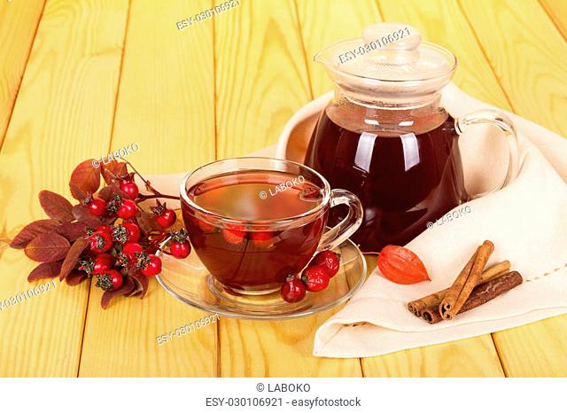 Jug and cup of rosehip drink, vanilla sticks on a background of light wood