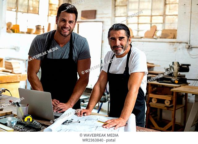 Portrait of two carpenters standing together in workshop