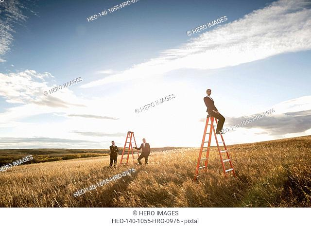 Businessmen looking at colleague sitting on ladder