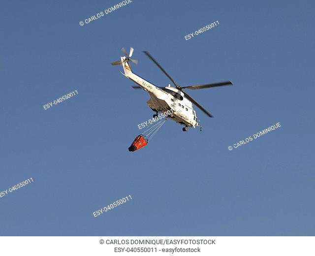 Fire fighting helicopter carrying water bag to drop in fire