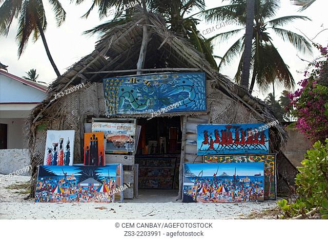 Paintings for sell in front of a traditional hut near the sea at the village, Nungwi, Zanzibar, Tanzania, East Africa