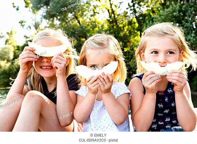 Portrait of three young sisters holding smiling melon in front of face in park