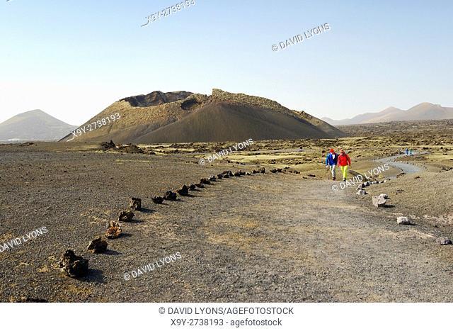 Crossing cinder field to volcanic cone of Caldera de los Cuervos. Timanfaya National Park, Lanzarote, Canary Islands, Spain