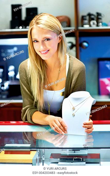 Beautiful blonde jewellery store clerk showing two necklaces on a bust display to the camera