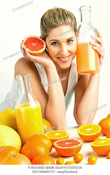 portrait of young woman with citrus fruit and orange juice