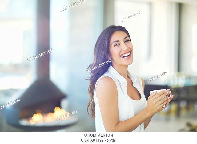 Portrait smiling woman drinking coffee near fireplace
