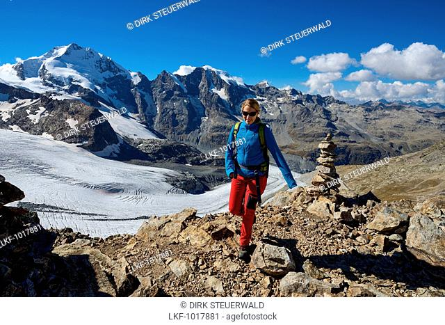 Woman at the summit of Piz Trovat (3146 m) with view to the Bernina-Alps with Bellavista (3922 m), Piz Bernina (4049 m), Piz Morteratsch (3751 m) as well as...