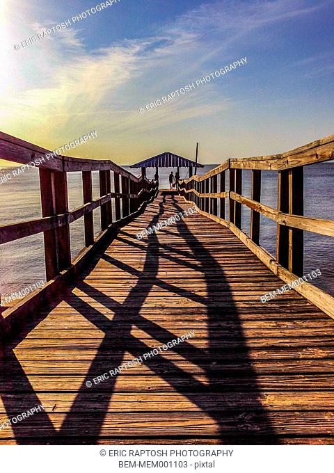 Shadows of railing on wooden dock at sunset