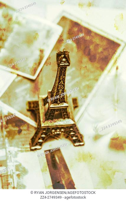 Sepia toned faded vintage image of nostalgic mementos of a Paris trip with an Eiffel Tower model standing on a scattered collection of old aged prints in a high...