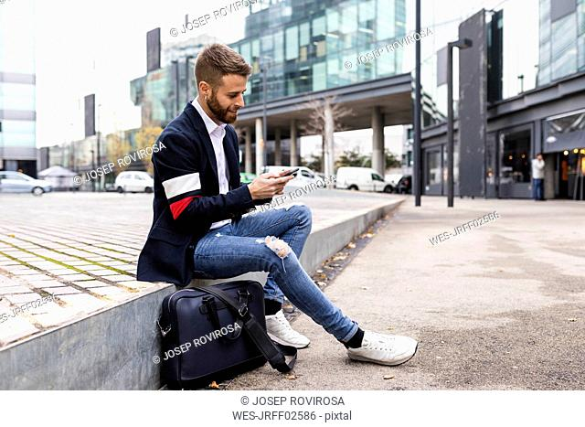 Stylish businessman sitting in the city using cell phone