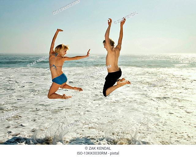 Couple leaping into waves on beach