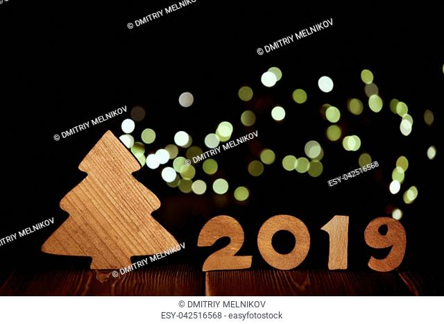 Wooden fir tree and text 2019 from wooden figure on dark wooden background with LED light garland. Horizontal view. New Year and Christmas