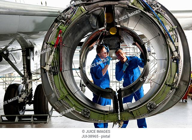Engineers inspecting engine casing of passenger jet in hangar