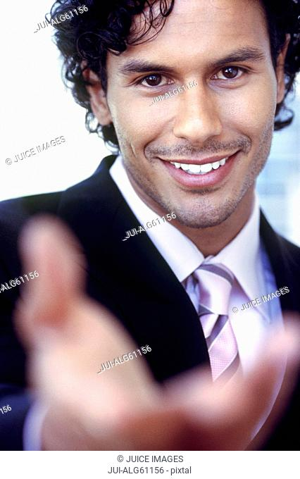 Young businessman gesturing viewer to approach, close-up