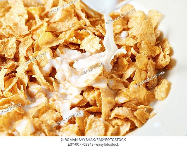 Corn flakes breakfast with milk being poured over it