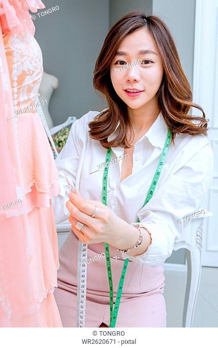 Young smiling female fashion designer