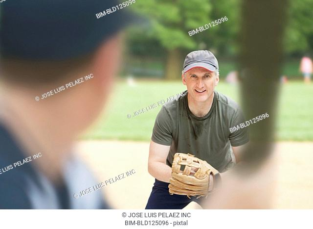Caucasian men playing baseball on field