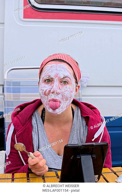 France, Bretagne, Finistere, Young woman applaying yoghurt face mask at camping ground