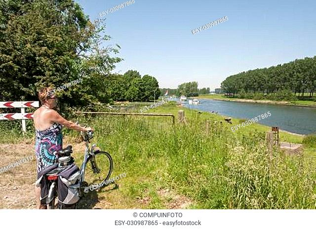 woman standing with bike looking at the boats going by on the river in Holland