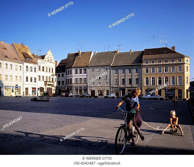 D-Torgau, Elbe, Sachsen, Buergerhaeuser am Marktplatz, Abendstimmung, zwei Kinder beim Spiel mit einem Fahrrad, junges Maedchen auf einem Fahrrad zieht einen...