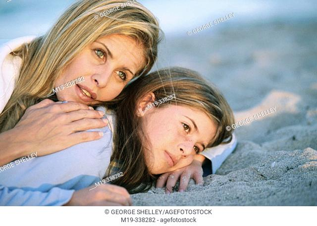 mother and daughter lying on the sand