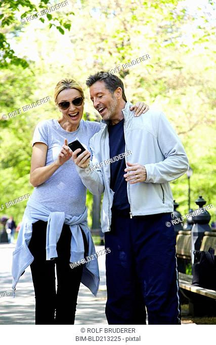 Caucasian couple using cell phone in park