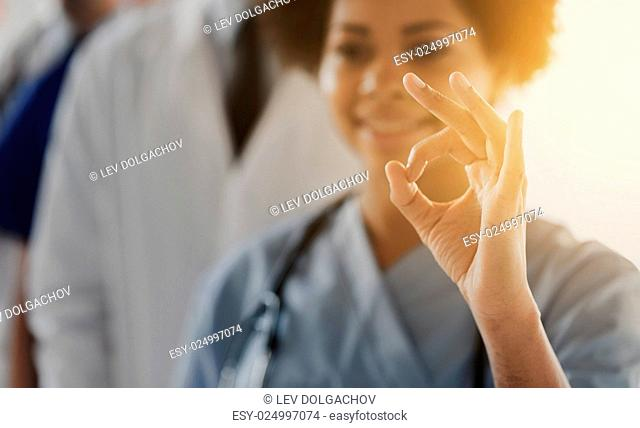 gesture, people and medicine concept - close up of happy female doctor or nurse showing ok hand sign over group of medics at hospital