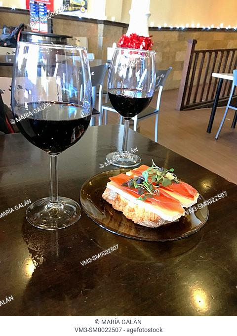 Two glasses of red wine and tapa of Iberian ham with cheese. Spain