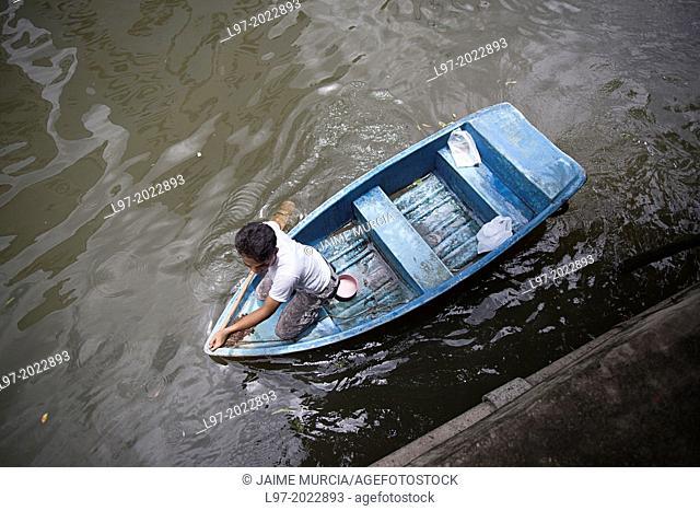 A man navigates his small boat along a canal, Bangkok Thailand