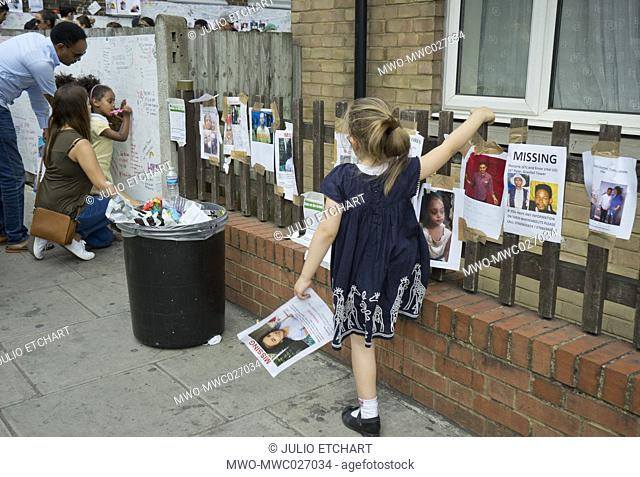 Visitors writing notes of condolence for victims of the fire disaster at the Grenfell Tower in London,England,UK