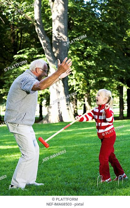 Girl and senior man playing croquet in the park Sweden