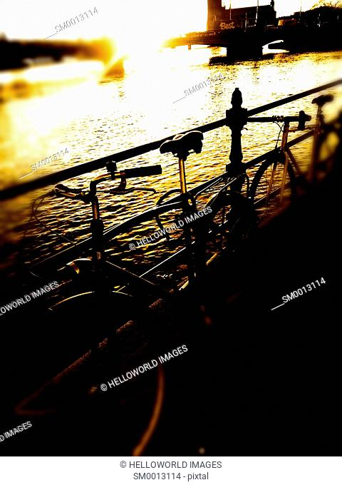 Bicycles at sunset and view towards Vasabron Bridge which crosses the natural waterway known as Norrstrom, Stockholm, Sweden, Scandinavia