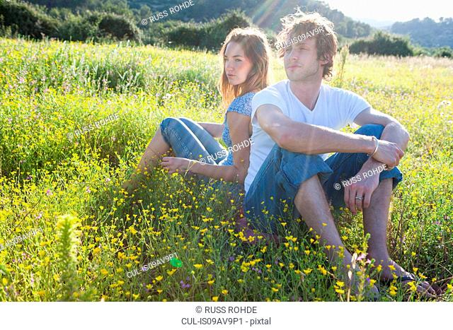 Romantic young couple sitting back to back in wildflower field, Majorca, Spain