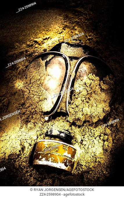 Dark eerie photo of a half buried gas mask in a shallow mass grave. Mass extinction event