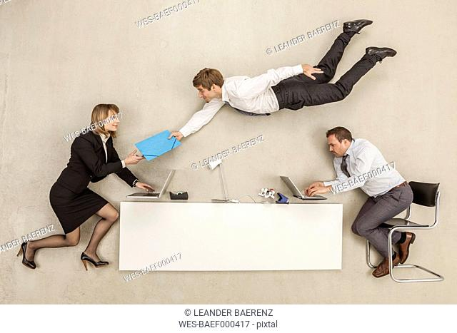 Business people working while another businessman providing file