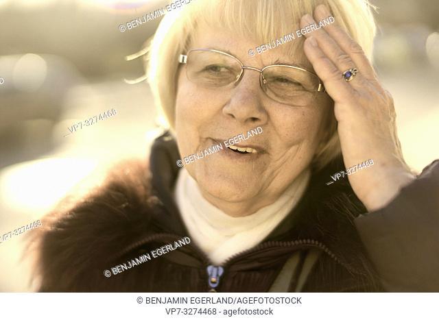 senior woman touching her forehead, in Cottbus, Brandenburg, Germany