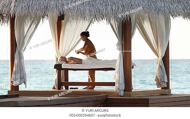 Woman receiving a back massage in a luxury seaside resort gazebo