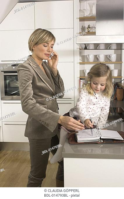 young businesswoman standing in kitchen and talking on cellphone while daughter is playing with her journal