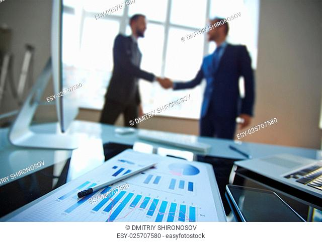 Business document at workplace with business partners handshaking on background