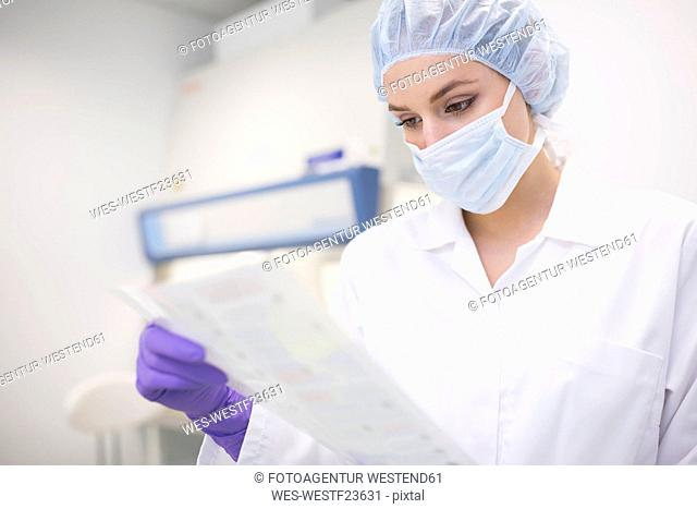 Scientist reading document in laboratory